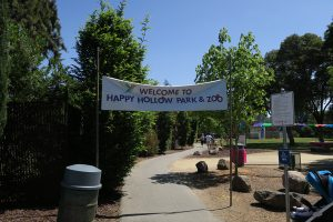 "entrance from back parking lot, sign says ""Welcome to Happy Hollow Park & Zoo"""