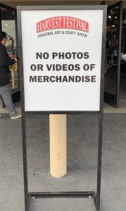 "Harvest Festival sign says ""no photos or videos of merchandise"""
