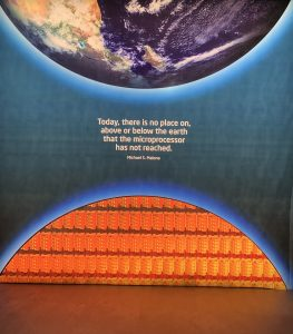 "Intel Museum poster of a quote that says, ""Today, there is no place on, above or below the earth that the microprocessor has not reached."" by Michael S. Malone"