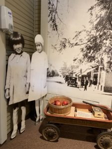 child's wagon with pretend fruit and cardboard cut-outs of children in an orchard, Campbell Historical Museum