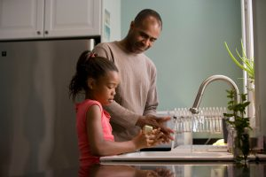 African-American father and daughter washing their hands