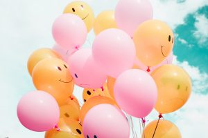 Bunch of pink and yellow balloons with happy faces on the yellow ones